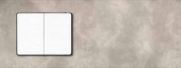 Czarny otwarty notatnik w linie na białym tle na tle betonu.