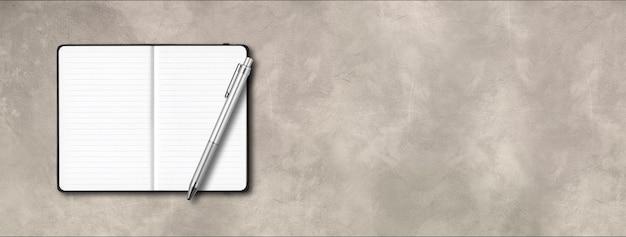 Czarny otwarty notatnik w linie z piórem na białym tle na tle betonu.