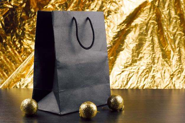 Czarny pakiet i błyszczące złote bombki na stole na tle goladen