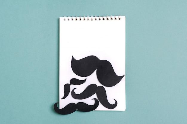 Czarny papier wąsy, notatnik na niebieskim tle darowizny miesięcy, koncepcja dzień ojca