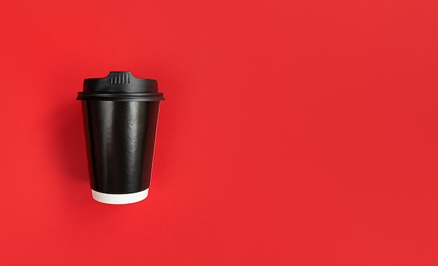 Czarny papierowy kubek kawy, aby przejść na czerwonym tle z miejsca na kopię.