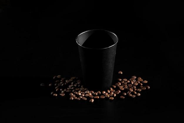 Czarny papierowy szkło na czarnym tle. ziarna kawy na ciemnym tle. dzień dobry