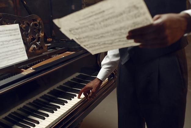 Czarny pianista z notatnikiem muzycznym w rękach na scenie z reflektorami. wykonawca pozuje na instrumencie muzycznym przed koncertem