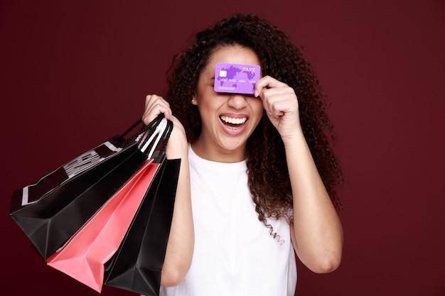 Czarny piątek. afro american dziewczyna w okularach trzyma torby na zakupy i kartę kredytową i uśmiecha się, na różowym tle