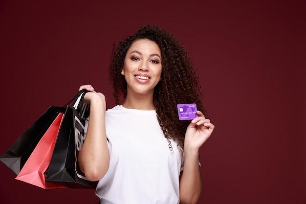 Czarny piątek afro american dziewczyna w okularach trzyma torby na zakupy i kartę kredytową i uśmiecha się na żółto