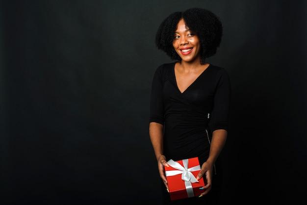 Czarny piątek. ciemnoskóra kobieta trzyma w rękach prezent noworoczny na czarnym tle