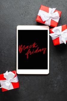 Czarny piątek - czerwone pismo na ekranie tabletu. pudełka na prezenty ze wstążkami. koncepcja świątecznych wyprzedaży.