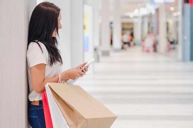 Czarny piątek, kobieta używa smartphone i trzymający torba na zakupy podczas gdy stojący na centrum handlowym