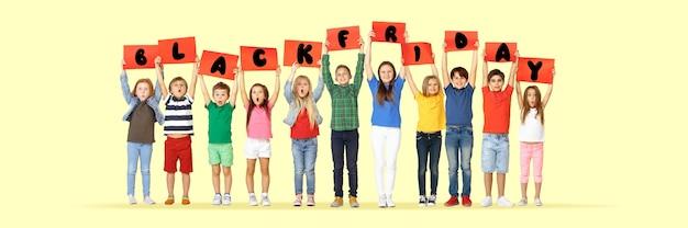 Czarny piątek, koncepcja sprzedaży. grupa dzieci, dzieci i młodzieży w jasnych ubraniach z emocjami szczęścia trzymających litery na żółtym tle. negatywna przestrzeń. kolorowy obraz do twojej reklamy.