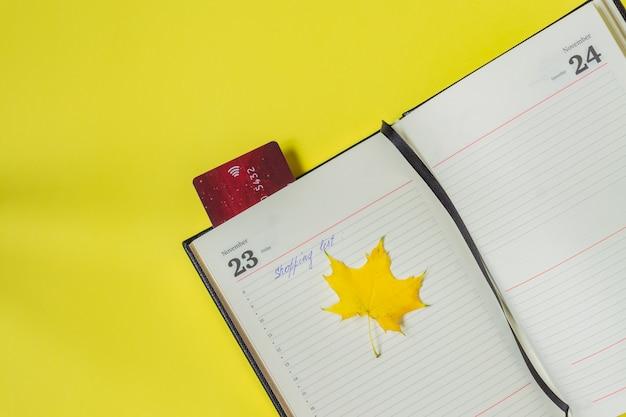 Czarny piątek koncepcja sprzedaży. lista zakupów w notatniku i karcie bankowej jako zakładka