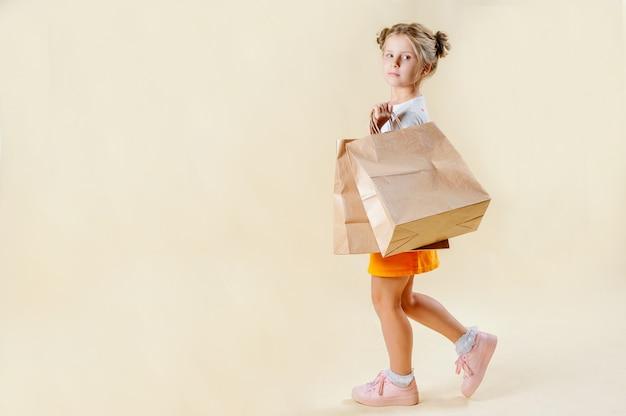 Czarny piątek. mała blondynki dziewczyna trzyma pakunki rzemieślnicze na lekkim stałym tle