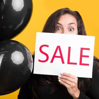 Czarny piątek model trzyma sztandar sprzedaży i balony