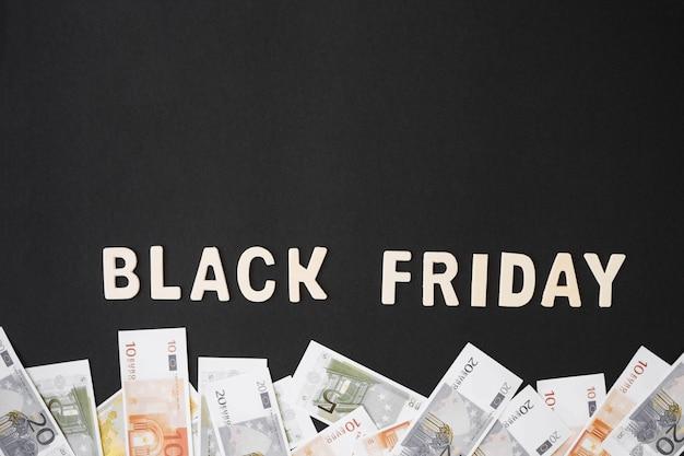 Czarny piątek napis z drewnianych liter z pieniędzmi