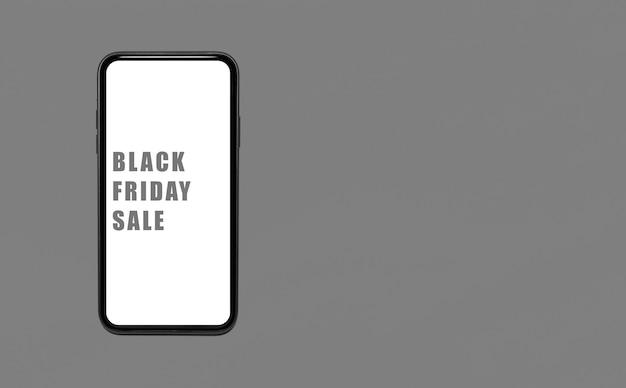 Czarny piątek sprzedaż tekst na ekranie smartfona. tło w kolorze szarym z miejsca na kopię.