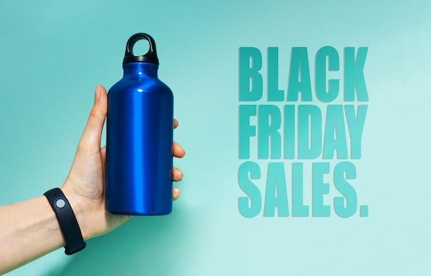 Czarny piątek sprzedaży tekst w pobliżu kobiecej ręki trzymającej aluminiową butelkę wody termo w kolorze niebieskim. tło błękitu, kolor aqua menthe.