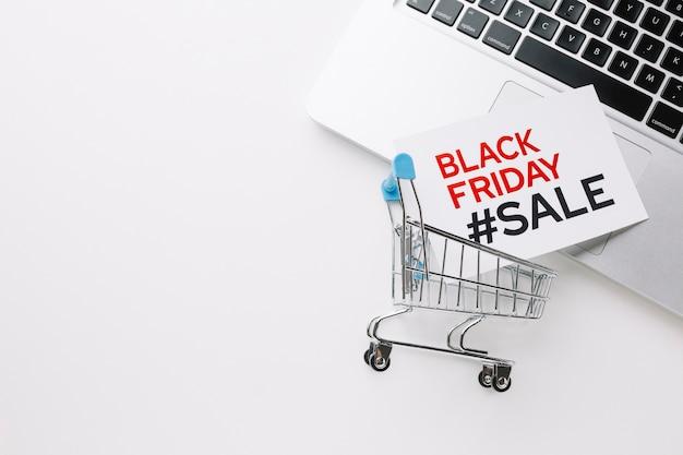 Czarny piątek wózek na zakupy i laptop z kopii przestrzenią