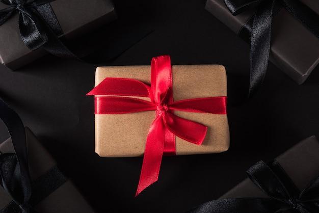 Czarny piątek wyprzedaż zakupów w pudełku upominkowym owiniętym czarnym papierem wokół brązowego pudełka z czerwoną wstążką