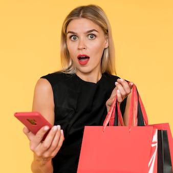 Czarny piątek zakupy zaskoczona kobieta z telefonem komórkowym