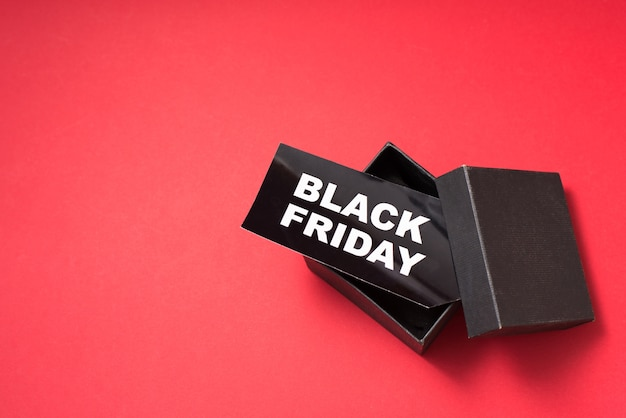 Czarny piątek. znacznik sprzedaży w pudełku na czerwonym tle