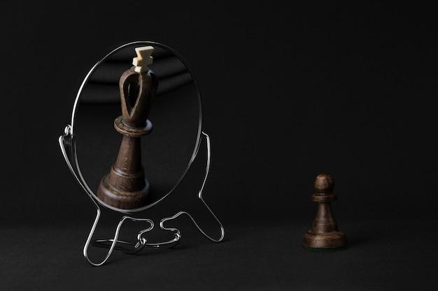 Czarny pionek widzi w lustrze czarnego króla