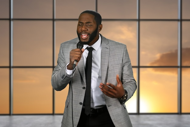 Czarny piosenkarz trzymając mikrofon.