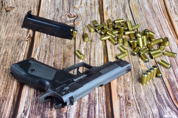 Czarny pistolet i kilka traumatycznych nabojów leżą na starych brązowych drewnianych deskach.