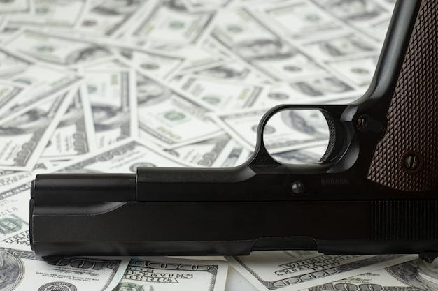 Czarny pistolet na stosie pieniędzy