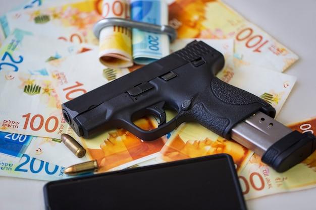 Czarny pistolet pistolet z amunicją i telefonem komórkowym na stosie pieniędzy nowy szekel izraelski banknotów na stole. półautomatyczna broń palna z rachunkami new israel shekel 100, 200 nis. waluta, przestępca