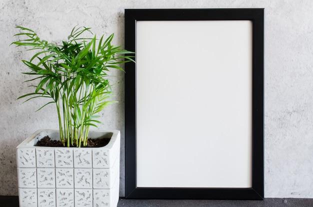 Czarny plakat lub ramka na zdjęcia i piękna roślina w doniczce betonowej