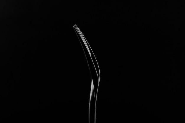 Czarny plastikowy rozwidlenie na czarnym tle. światło konturowe. niski klucz.
