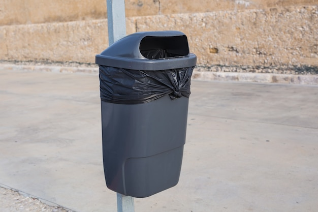 Czarny plastikowy śmietnik na ulicy.