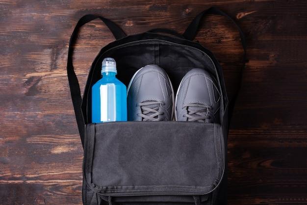 Czarny plecak treningowy z trampkami i niebieską butelką na napoje izotoniczne, aby przywrócić równowagę wody i soli, sport i zdrową koncepcję, z bliska.