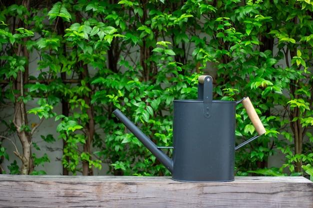 Czarny podlewanie garnek na drewnianym z zielonym drzewem na tle