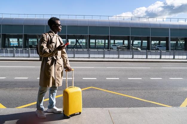 Czarny podróżnik mężczyzna z walizką stoi w terminalu lotniska trzymając telefon, szukając taksówki