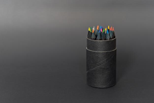 Czarny pojemnik na ołówki, pełen kolorowych kredek na ciemnym tle