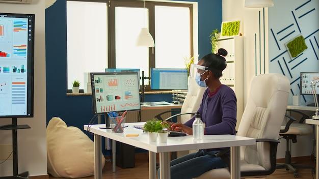 Czarny pracownik z maską ochronną i przyłbicą do czyszczenia rąk żelem odkażającym przed pisaniem do komputera. kobieta w nowym normalnym miejscu pracy dezynfekuje, podczas gdy koledzy pracują w tle
