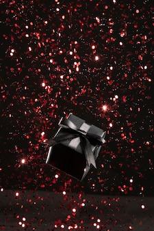 Czarny prezent z asortymentem czerwonych brokatów