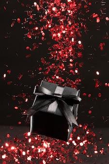 Czarny prezent z bliska aranżacja czerwony brokat