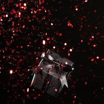 Czarny prezent z bliska czerwony brokat