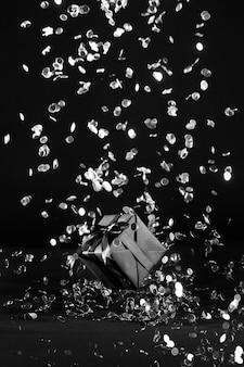 Czarny prezent z czarnym konfetti dookoła