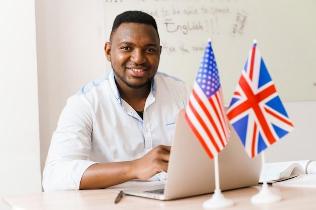 Czarny przystojny mężczyzna używa swojego laptopa do pracy online zgodnie z dystansem społecznym