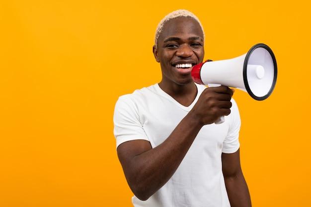 Czarny przystojny uśmiechnięty amerykański mężczyzna w białej koszulce mówi wiadomości przez megafon na odosobnionej pomarańcze