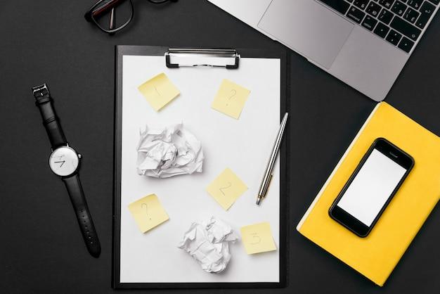 Czarny pulpit biurowy z białą kartką papieru z bezpłatną przestrzenią do kopiowania i długopisem, laptopem, okularami, zegarkiem i zmiętymi papierowymi kulkami.