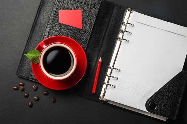 Czarny pulpit biurowy z notatnikiem, kartą kredytową i czerwoną filiżanką kawy. widok z góry.
