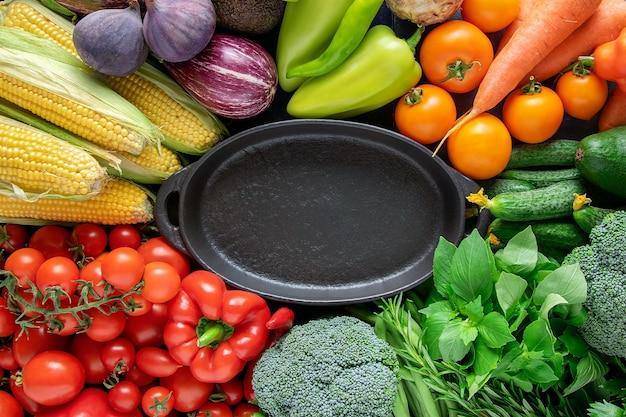 Czarny pusty talerz na tle świeżych, jasnych organicznych warzyw.