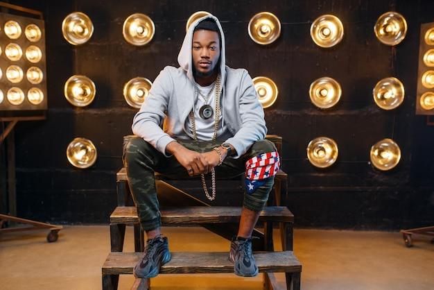 Czarny raper w bluzie z kapturem siedzący na schodach, występ na scenie
