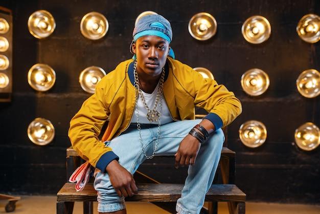 Czarny raper w czapce siedzi na schodach