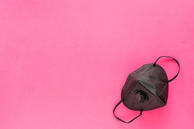 Czarny respirator na różowym. medyczna maska ochronna na twarz