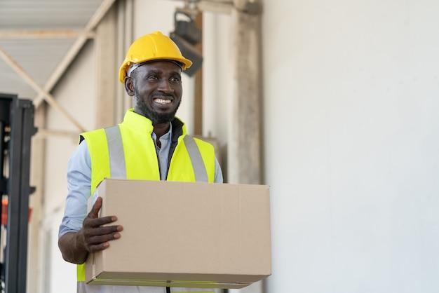 Czarny robotnik w kamizelce odblaskowej i żółtym kasku, trzymając karton przygotowuje produkt do wysyłki w fabryce magazynu