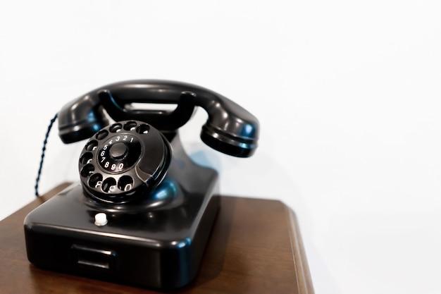 Czarny rocznika telefon na drewnianym stole